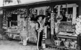 Print of a postcard showing Mario Valadez in Mexican dress standing in front of his Olvera Street...
