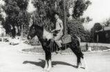 Young man riding a horse at family home in the San Fernando Valley