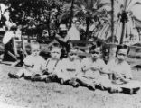 Quon brothers as infants, five young boys sitting on the grass in front of benches