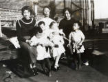 Howard Quon's mother, Jeong Shee Quon, is sitting in the middle between two other women and four...
