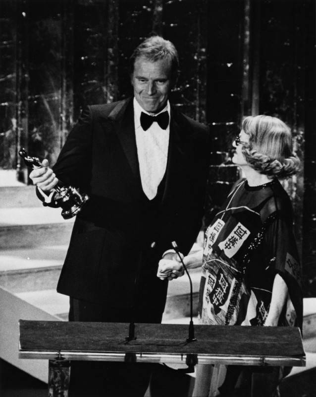 Bette is shown presenting the Jean Hersholt Humanitarian Award to actor Charlton Heston at the 50th Academy Awards