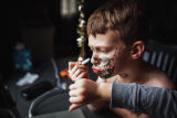 Boy drawing on his face with a marker while participating in an online social gathering during the...