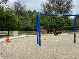 Child playing in an empty playground with roped off swing set
