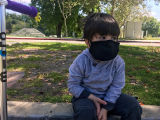 Seated, masked toddler at an empty park looking pensive