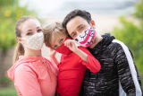 Family wearing masks take a portrait photograph