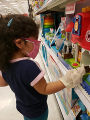 Child looking at toys at Target while wearing masks and gloves
