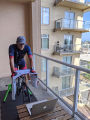 Man training on a stationary bicycle on balcony