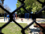 Empty playground viewed through a metal chain link fence