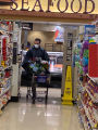 Man wearing a mask and rain poncho pushing a shopping cart inside a grocery store