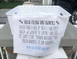 Plastic bin with a sign encouraging passersby to pick up free dog treats and potty bags