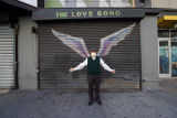 Man poses in front of angel wings painted on a storefront shutter