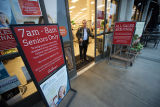 Employee monitors Gelson's supermarket entrance amid signs announcing designated shopping times...