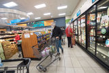Masked man shops at a busy Gelson's supermarket during the COVID-19 pandemic
