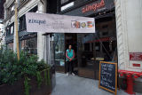 Man stands at the entrance of Zinque restaurant