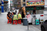 Construction workers pause for a meal at a sidewalk eatery