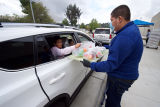 Children in a car pick up meals from a Grab and Go Food Center