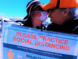 Masked woman kissing an unmasked man and holding a COVID-19 prevention poster