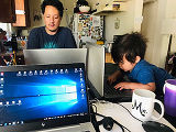 Father telecommuting while toddler plays on a computer