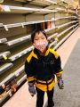 Young boy posing in front of empty shelves at a grocery store