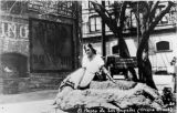 Postcard of girl sitting on water trough at north end of Olvera Street, Italian Hall at left.