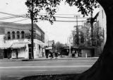Shot of Olvera Street looking north to cross. Trolly lines, plaza tree, and people at the cross...