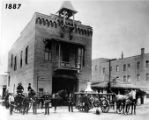 Photograph of a group of firemen standing in front of the Firehouse, built in 1884 just south of...