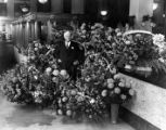 Harry Chandler surrounded by baskets of flowers