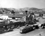 Overview of Church, Spanish store front signs, trolley car and bus on North Main street