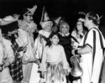 Girl surrounded by adults in costume