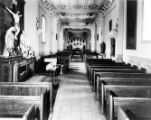 Plaza Church interior looking toward altar,  Jesus on cross at left, tile floors and wood pews