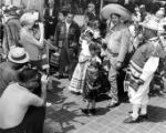 Group taking pictures of men and children in Mexican costumes