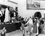 Priest and a man standing on stage with group of people waiting for their animals to be blessed.
