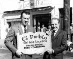 "Hubert Laugharn holding the ""El Pueblo..."" sign with Mayor Yorty"