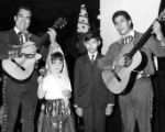 Los Amigos: Boy and girl with Mariachis at Las Posadas party
