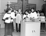 Priest and altar boys blessing the interior of the Simpson building