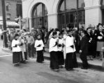 Priest and altar boys walking in front of the Simpson building holding candles and crucifix