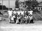 Baseball team photo with men in white shirts holding a trophy