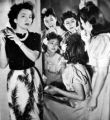Crowded round a mirror, four of the girls Look Magazine took to Luke Field for an all-Chinese...