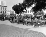 Crowd sitting in chairs watching a conert at the kiosko