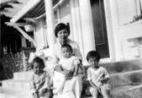 In front of house, Soy Wan Tong Lung (mother) and left to right: Dorothy, May and Joe Lung