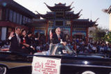 Poy Wong riding a black convertible representing the CCBA in the Los Angeles Golden Dragon Parade