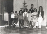 Children posed in front of a small Christmas tree with tinsel.