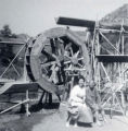 "A woman and a man seated in front of a waterwheel. On the back of the photo it reads ""Slosson..."
