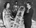Man presents scroll featuring Chinese characters. In the top center is a seated Buddha figure