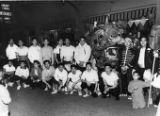 Group of young men posing with a dragon in front of Emory Chow Insurance Agency