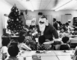 Gerald Jann dressed as Santa Claus entertaining a class at the Castelar School