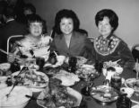 Photo of Lily Chan, left, and Mrs. Ann Lew, far right, eating dinner
