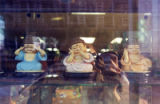 Three Buddha statues in a store window in San Gabriel Square