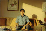 Henry Quan seated on a couch