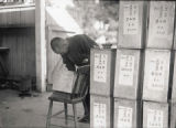 Chinese man with metal boxes, each of which contains human remains